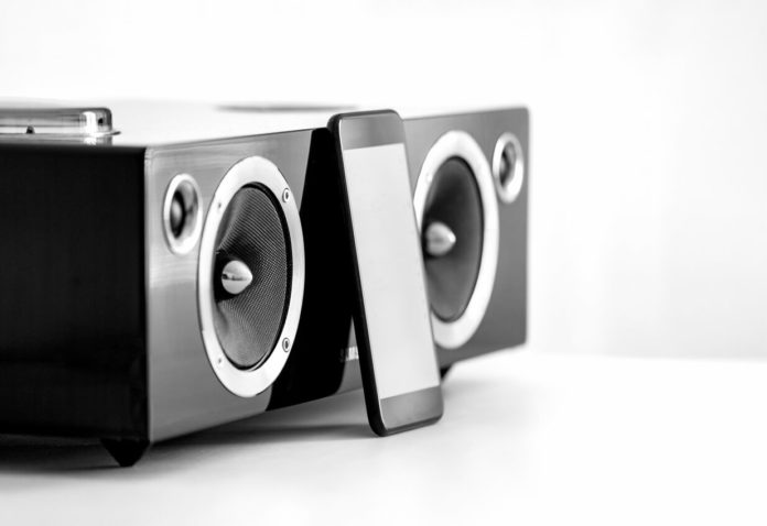 an image of a bookshelf stereo with an iphone resting on it